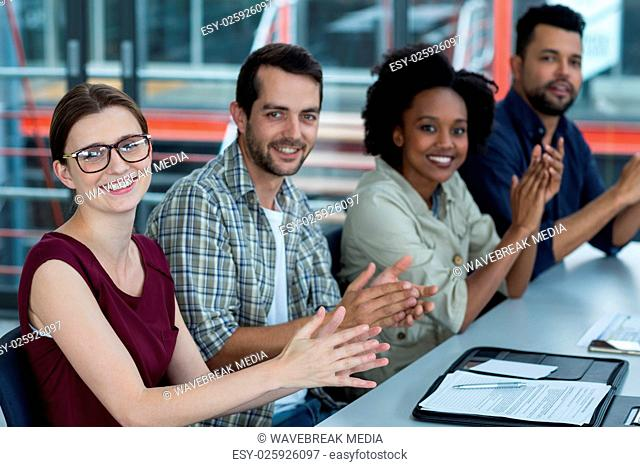 Smiling business executives clapping in meeting at office