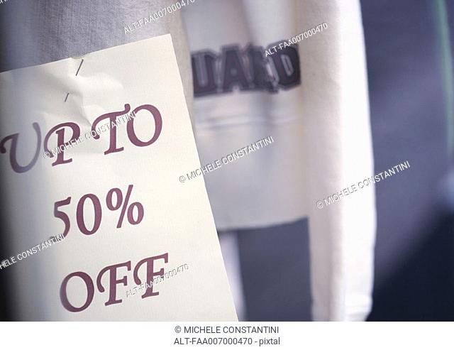 'Up to 50 off' sign pinned to clothing