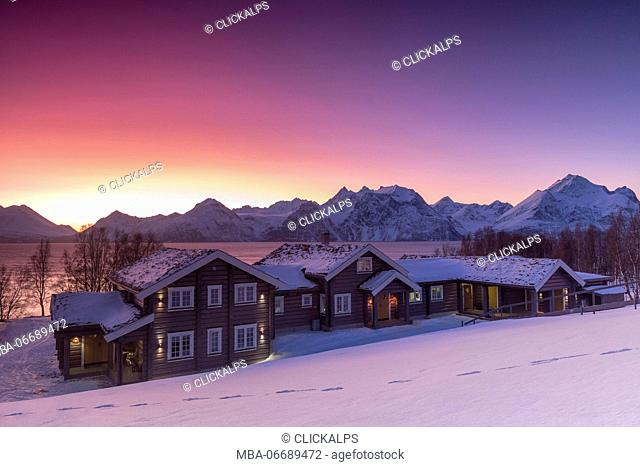 Lyngen Lodge illuminated by the light of the Arctic sunset. Hammarvika, Lyngenfjord, Lyngen Alps, Troms, Norway, Lapland, Europe