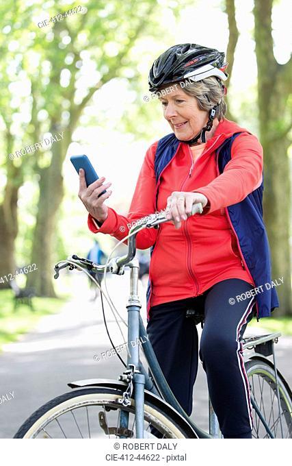 Active senior woman using smart phone on bike in park