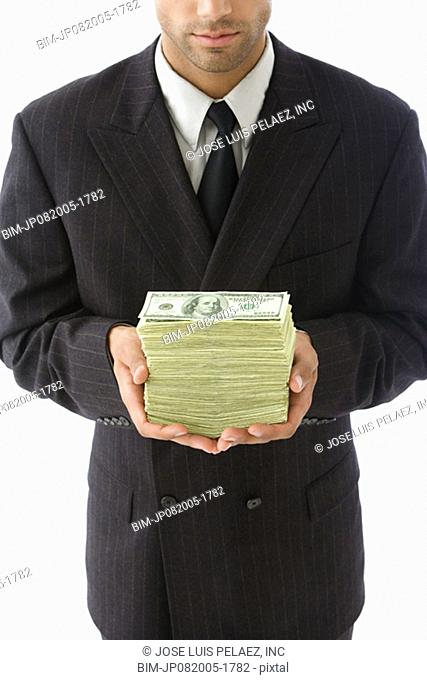 Businessman holding stack of twenty dollar bills in hands
