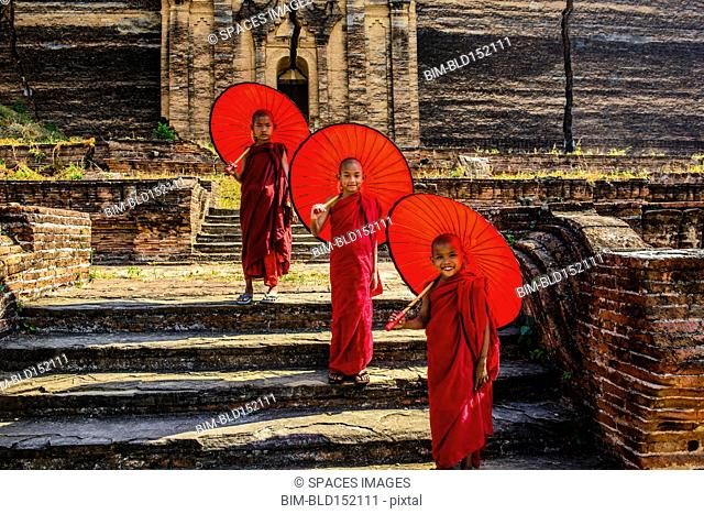 Asian monks standing under umbrellas near historic temple, Mingun, Mandala, Myanmar