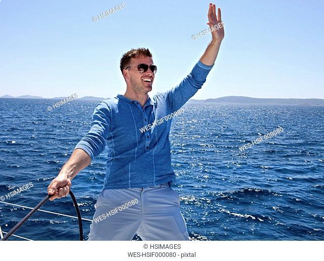 Croatia, Zadar, Young man waving from sail boat