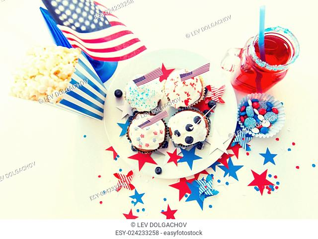 celebration, patriotism and holidays concept - close up of glazed cupcakes decorated with american flags, juice glass or mason jar