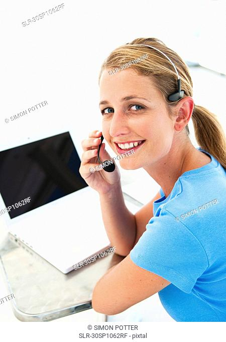 Happy woman in office with headset