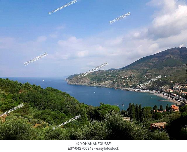 An amazing caption of the beautiful places from the 5 Terre in Liguria with an amazing blue sky and some green mountains in the background