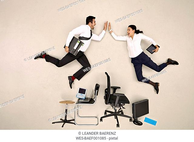 Business colleagues flying over chairs high fiving