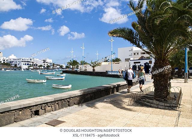 ARRECIFE LANZAROTE Houses and boats people walking promenade inner harbour lagoon