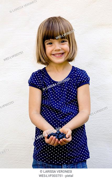 Portrait of little girl with two handfuls of blueberries