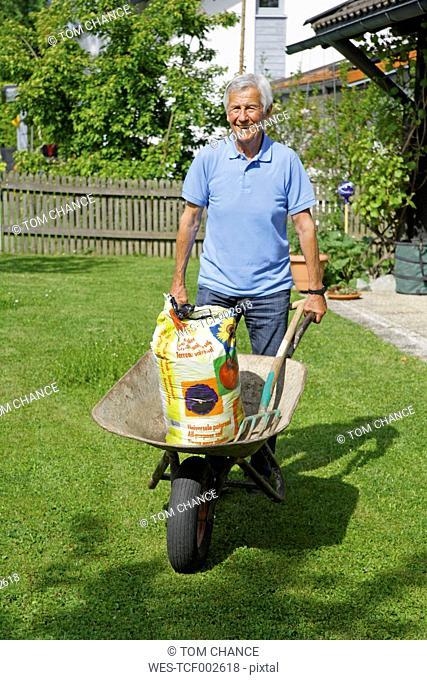 Germany, Bavaria, Senior man with wheelbarrow in garden