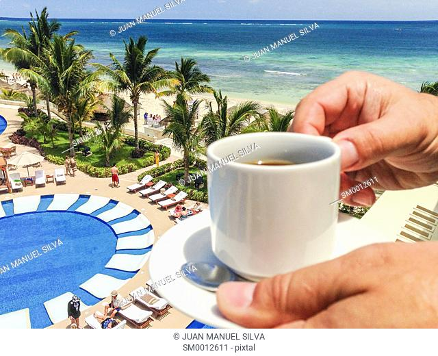 Man holding cup of coffee on balcony of beach resort