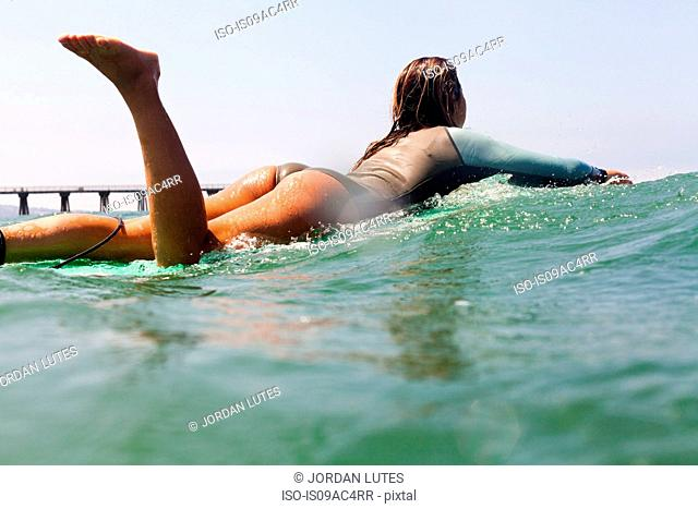 Young woman on surfboard, Hermosa Beach, California, USA
