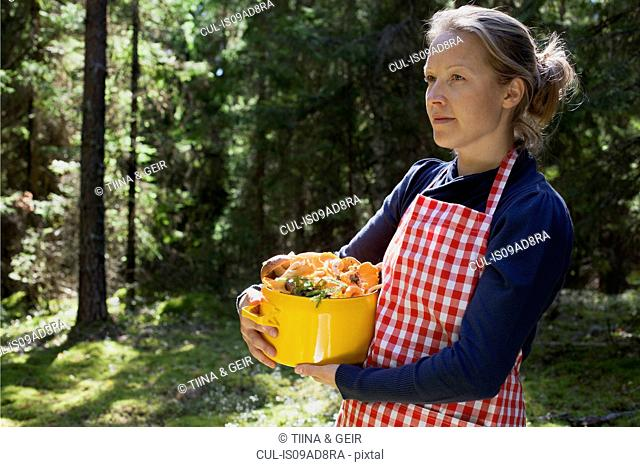 Woman in forest with mushrooms in saucepan