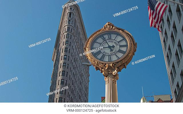 STATIC LOCKED DOWN TIME LAPSE WIDE SHOT LOW VIEW PUBLIC CLOCK FLAT IRON BUILDING FIFTH AVENUE NEW YORK CITY USA