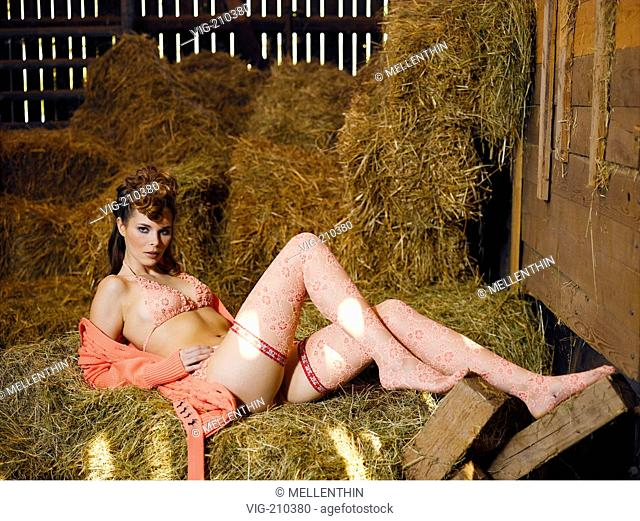 Young woman lying on hay bales in a stable.  - G³ltlingen, GERMANY, 30/08/2005