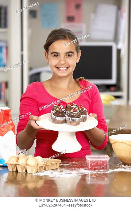 Girl With Homemade Cupcakes In Kitchen