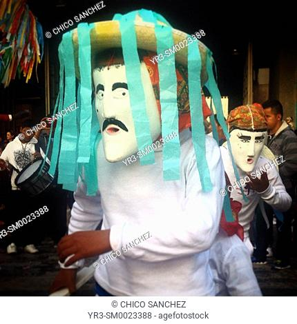 Men wearing white masks dance during the annual pilgrimage to the Our Lady of Guadalupe basilica in Mexico City, Mexico