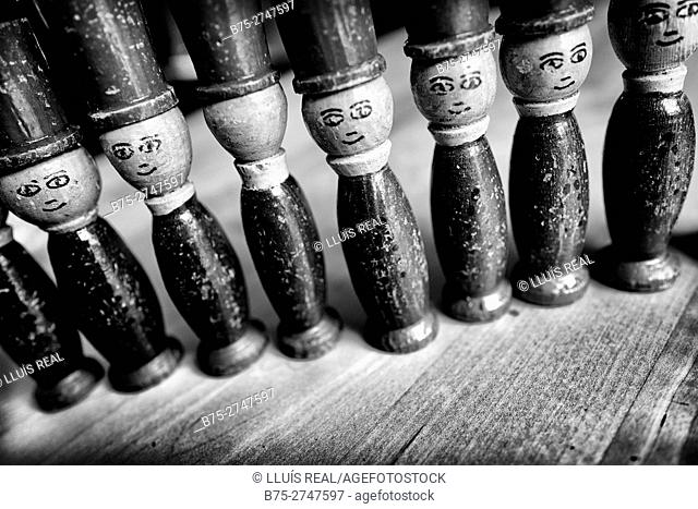 Group of wooden bowling pins of a child vintage game looking at the camera, one looking back
