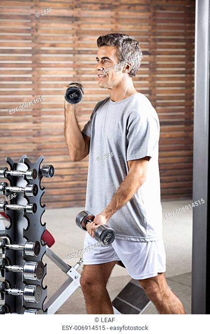 Young man lifting dumbbells in health center