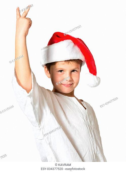 Very beautiful seven year old boy in a red cap. He shows two fingers victory. Picture taken on a white background