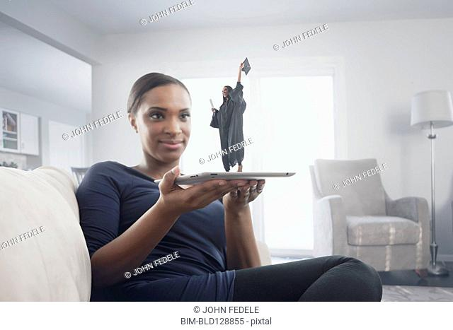 Black woman watching figure of graduate standing on digital tablet