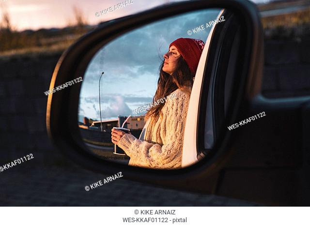 Iceland, young woman with coffee to go at sunset, mirrored in wing mirror