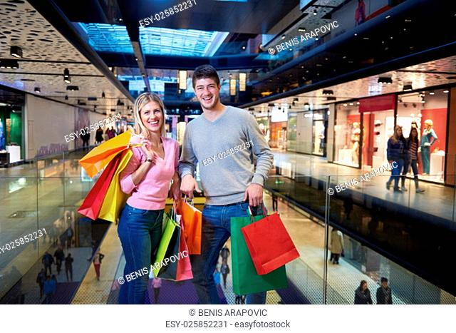 young couple with shipping bags in modern mall