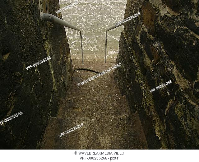 Concrete stairs leading into the grey choppy ocean. Cork, Ireland