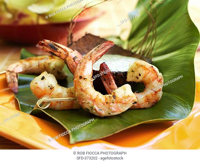 Grilled coconut prawns with coconut dip on banana leaf