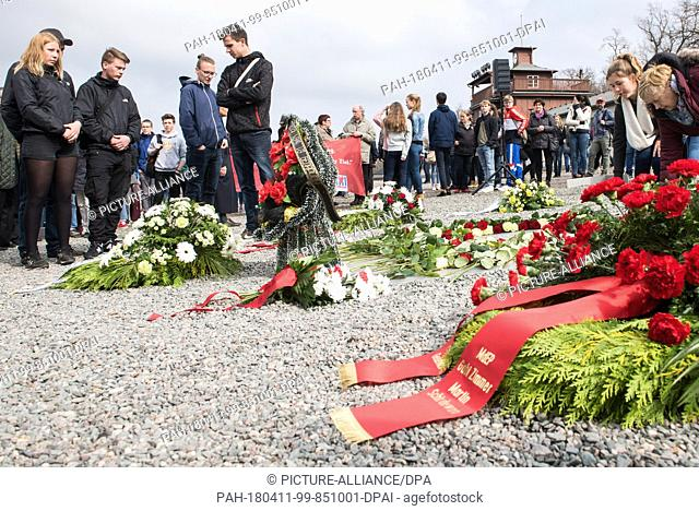 11 April 2018, Germany, Weimar: Participants place flowers on a memorial plaque of the former Nazi concentration camp Buchenwald for the 73rd anniversary of the...