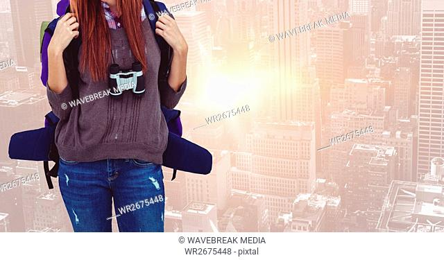 Woman with backpack and camera standing against cityscape