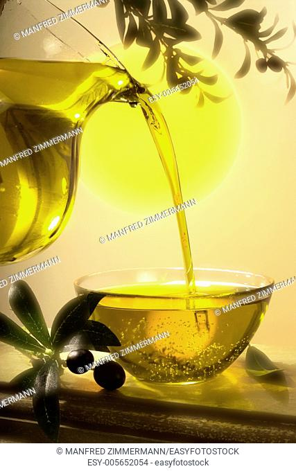 golden Olievenoel flows from glass jug in glass bowl