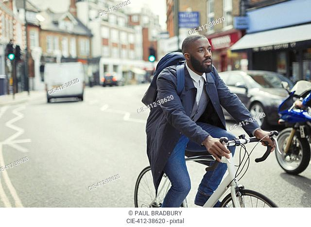 Businessman commuting, riding bicycle on urban street