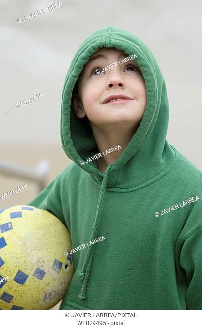 Boy holding a ball at beach. Hendaye. Aquitaine, France
