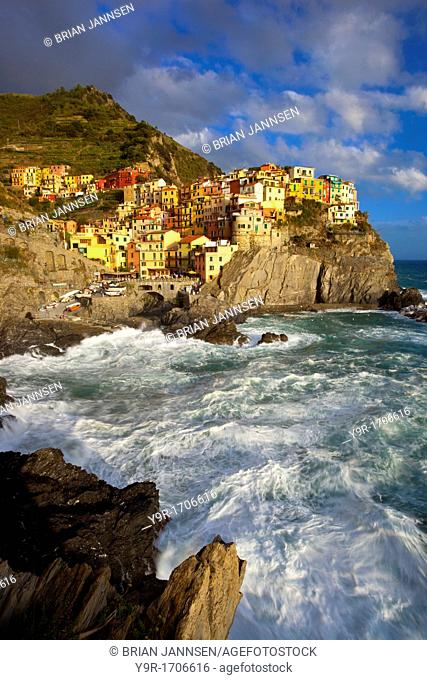 Swirling ocean at the foot of medieval town of Manarola in The Cinque Terre, Liguria Italy