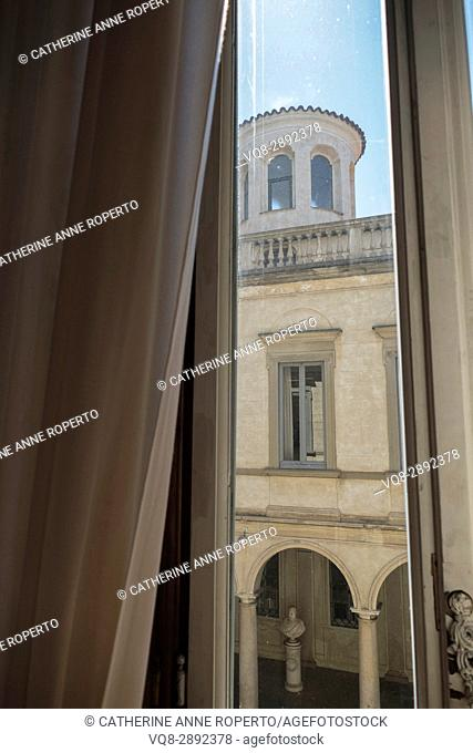 Warm summer breeze through palazzo window looking onto classical courtyard with columns and balustrade, Milan, Italy