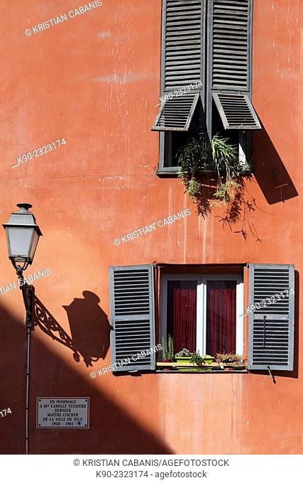Red facade of an old house with green wooden window shades in the old quarter of Nice, South of France, Europe