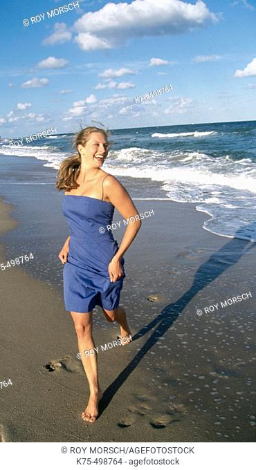 Happy young woman running on beach