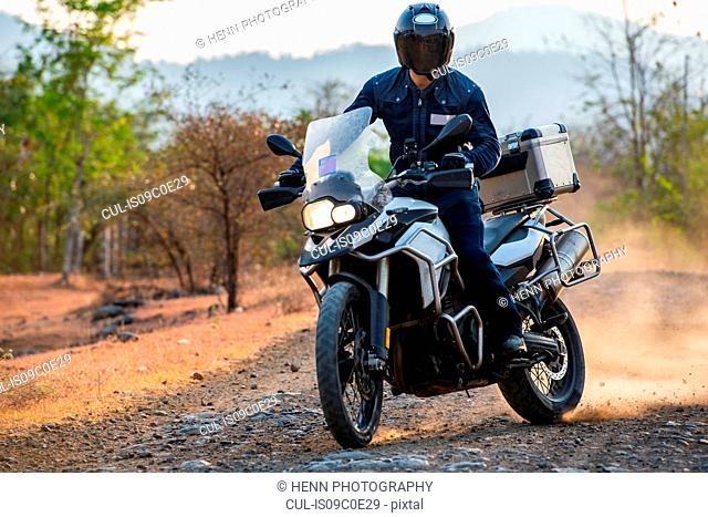 Man riding ADV motorcycle on dirt road in Cambodia