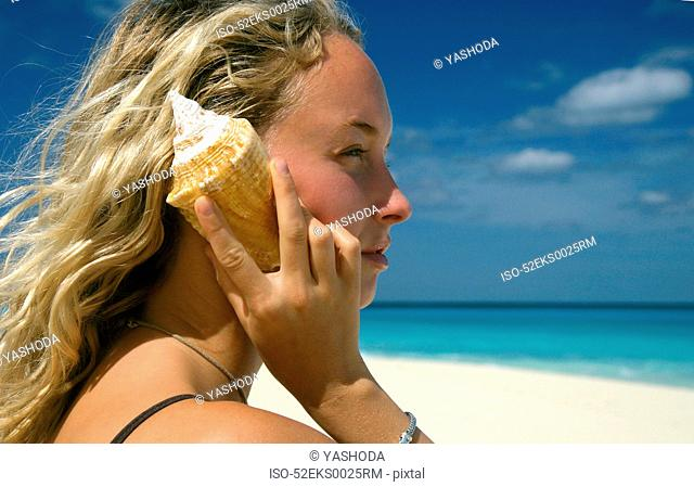 Woman holding shell by ear at beach