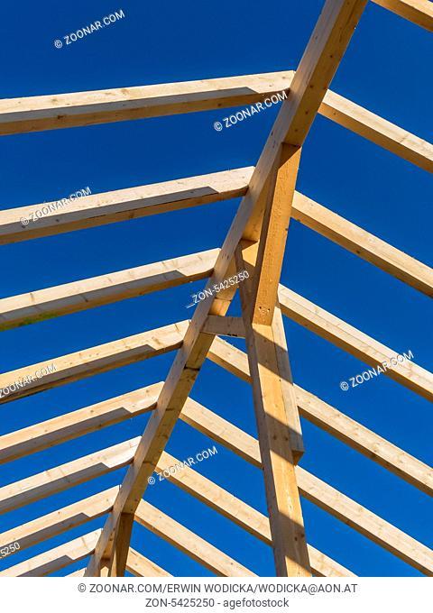 Auf einem Haus wird auf einer Baustelle ein neues Dach gebaut. Träger aus Holz für Dachstuhl