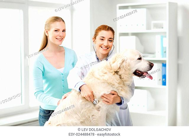 medicine, pet, animals, health care and people concept - happy woman and veterinarian doctor with stethoscope checking up golden retriever dog at vet clinic