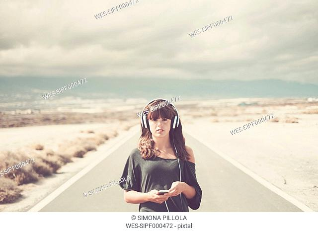 Young woman on the road listening music with headphones
