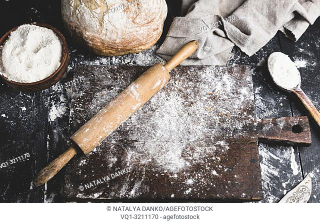 baked bread, white wheat flour, wooden rolling pin and old cutting board on a black table, top view