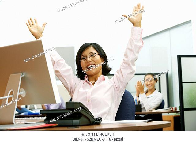 Asian businesswoman cheering at desk