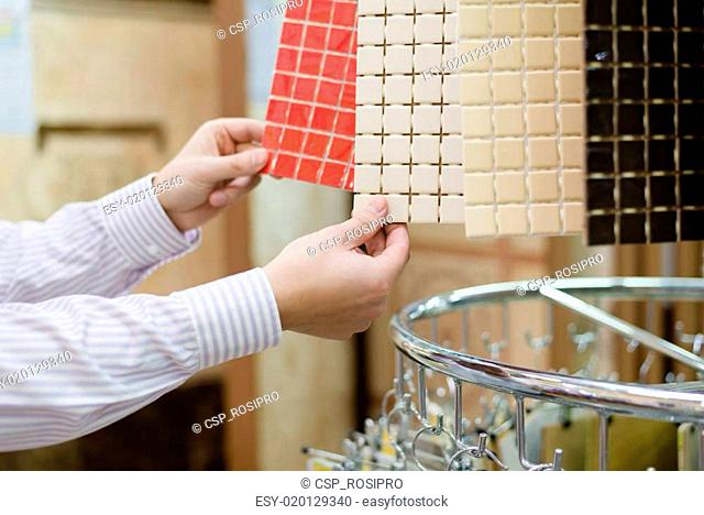 closeup on hands of choosing buyer or employee presenting colorful tiles in a supermarket or DIY department store on the display shelf background