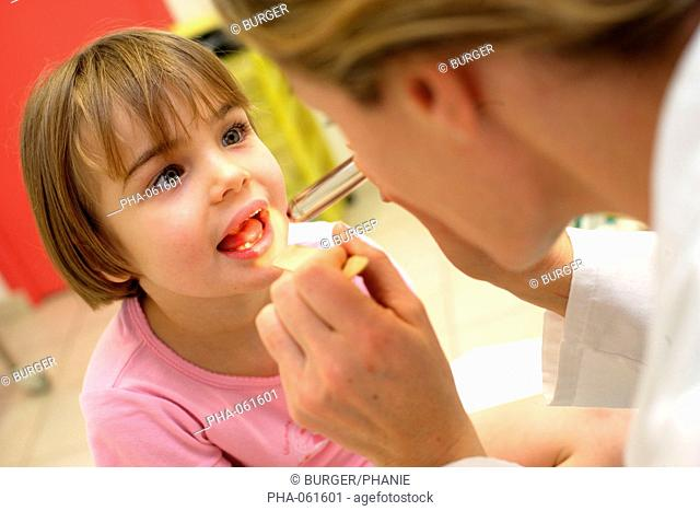A pediatrician examines the throat of a 4 years old child