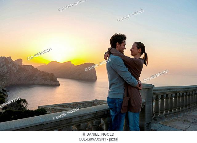 Mid adult couple on balcony, hugging, face to face, sunset