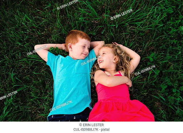 Overhead portrait of boy and sister lying on grass looking at each other