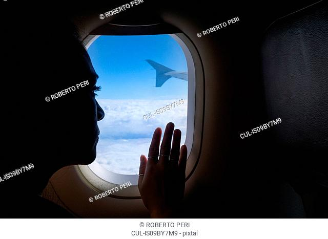Woman travelling in airplane, looking out window